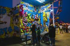 Okręgu administracyjnego jarmark przy nocą, gry na midway Obraz Stock