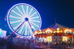 Okręgu administracyjnego jarmark przy nocy Ferris kołem na Midway zdjęcia royalty free