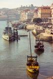 Okręt marynarki i tradycyjne drewniane rabelo łodzie z wino baryłkami na Douro rzece w Porto, Portugalia zdjęcie royalty free