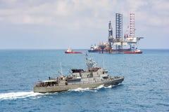 Okręt wojenny patroluje chronienie wieżę wiertniczą Fotografia Royalty Free