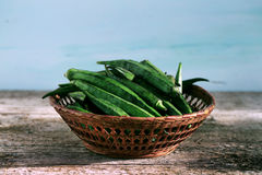 Okra or bhindi, bamia stacked in a basket on wood background Royalty Free Stock Image