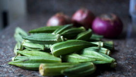 Okra with onions in the background. A vegetable used in making african soup Stock Photography