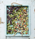Okra, spicy peppers and small black corns on blue wooden tray over light rustic backdrop, top view. Stock Photography