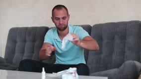 Okropna alergia Sfrustowany przystojny młodego człowieka kichnięcie i używać tkanka podczas gdy siedzący na leżance w domu zbiory