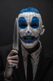 Okropny błazen i Halloween temat: Szalony błękitny błazen w czarnym kostiumu z nożem w jego ręce odizolowywającej na ciemnym tle  Fotografia Stock