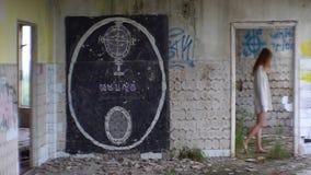 Okropny zaniechany budynek z graffiti na ścianach Widok szalenie niewiadoma czerwieni głowy kobieta w białym koszulowym odprowadz zbiory wideo