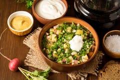Okroshka Kalte Suppe des traditionellen russischen Sommers mit Wurst, Gemüse und Kwaß in der Schüssel auf hölzernem Hintergrund Lizenzfreies Stockfoto