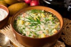 Okroshka Kalte Suppe des traditionellen russischen Sommers mit Wurst, Gemüse und Kwaß in der Schüssel auf hölzernem Hintergrund Stockfotografie