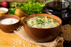 Okroshka Kalte Suppe des traditionellen russischen Sommers mit Wurst, Gemüse und Kwaß in der Schüssel auf hölzernem Hintergrund Stockfotos