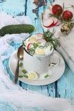 Okroshka on kefir on a blue wooden background. Okroshka on kefir with radish and cucumber and quail egg on a blue wooden background Stock Image