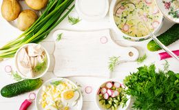 Okroshka. Russian food. Ingredients for cooking summer yogurt cold soup with egg, cucumber, chicken and dill on wooden table. Okroshka. Russian food. Top view stock photography
