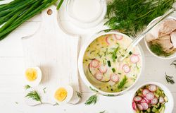 Okroshka. Russian food. Ingredients for cooking summer yogurt cold soup with egg, cucumber, chicken and dill on wooden table. Okroshka. Russian food. Top view royalty free stock photography