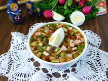 Okroshka. Russian traditional cold soup okroshka on a white tissue on a wooden table surrounded by vegetables stock photos