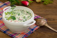 Okroshka. Summer light cold yogurt soup with cucumber, radish, eggs and dill on a wooden table. Wooden background. Close-up. Top v Royalty Free Stock Image