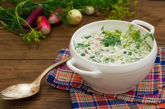 Okroshka. Summer light cold yogurt soup with cucumber, radish, eggs and dill on a wooden table. Wooden background. Close-up. Top v Stock Image