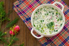 Okroshka. Summer light cold yogurt soup with cucumber, radish, eggs and dill on a wooden table. Wooden background. Close-up. Top v Royalty Free Stock Photos
