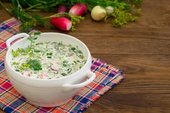 Okroshka. Summer light cold yogurt soup with cucumber, radish, eggs and dill on a wooden table. Wooden background. Close-up. Top v Stock Photos