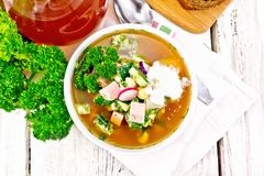 Okroshka in white bowl on board top. Cold soup okroshka from sausage, potatoes, eggs, radish, cucumber, greens and kvass in a white bowl on napkin, bread and jug Royalty Free Stock Photography