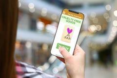 Okrucieństwo bezpłatny pomysł, dziewczyna z bezszkieletowym telefonem na zamazanym centrum handlowego tle fotografia stock