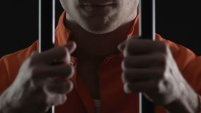 Okrutni seryjnego zabójcy mienia więzienia komórki bary, więzień wręczają zbliżenie, prawa łamanie zbiory wideo