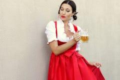 Oktober-Festkonzept Schöne deutsche Frau im typischen oktoberfest Kleiddirndl, der ein Maß hält Stockbild