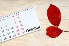 Oktober-Kalender, Rotblätter auf Holztisch Stockfotografie