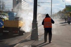 Oktober 2017 Moskau, Russland Eine Arbeitskraft in einer orange Weste wie Papier und Schmutz von den Straßenrandsäulen Lizenzfreie Stockfotos