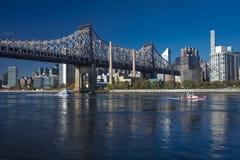 24 OKTOBER, 2016 - NEW YORK - Queensbrug aan Roosevelt Island in ochtendlicht op de Rivier van het Oosten toont Rode Boot Stock Afbeelding