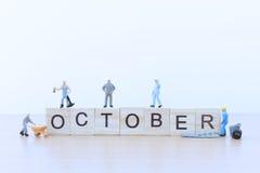 Oktober ord med miniatyrfolkarbetaren Arkivfoto