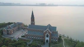 19 Oktober, 2018 Suzhoustad, China Luchthommelvlucht over katholieke kerk dichtbij het meer op de zonsondergang stock footage