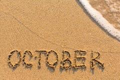 Oktober - Wort gezeichnet auf den Sandstrand mit der weichen Welle Lizenzfreies Stockfoto
