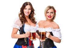 oktoberfest啤酒啤酒杯的两个美丽的白肤金发和深色的女孩 免版税图库摄影