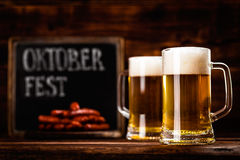 Oktoberfest beer. Oktoberfest background with two mugs of beer and sausages royalty free stock photo