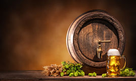 Oktoberfest beer barrel and beer glass. With wheat and hops on wooden table stock photography