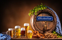 Oktoberfest beer barrel and beer glasses. With wheat and hops on wooden table Stock Image