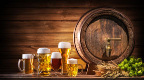 Oktoberfest beer barrel and beer glasses. With wheat and hops on wooden table stock photo