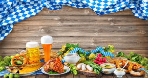 Oktoberfest. Beer, pretzels and various Bavarian specialties on wooden background royalty free stock images