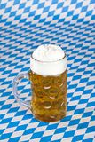 Oktoberfest beer stein on Bavarian flag Stock Image