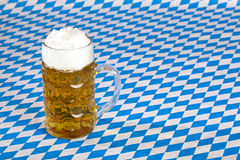 Oktoberfest beer stein on Bavarian flag Stock Photos