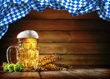 Oktoberfest beer with wheat and hops. On wooden table royalty free stock photos