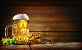Oktoberfest beer with wheat and hops. On wooden table stock photography