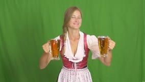 Oktoberfest. Blonde woman holding beer mugs on an isolated background. Oktoberfest. Blonde woman holding beer mugs on an isolated green background royalty free stock photo