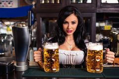 Oktoberfest. Brunette woman holding beer mugs in bar Royalty Free Stock Image
