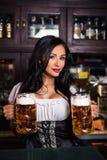 Oktoberfest. Brunette woman holding beer mugs in bar Royalty Free Stock Photo