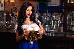 Oktoberfest. Brunette woman holding beer mugs in bar Stock Photo