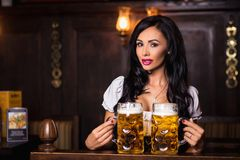 Oktoberfest. Brunette woman holding beer mugs in bar Royalty Free Stock Images