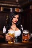 Oktoberfest-Brunettefrau, die Bierkrüge in der Bar hält stockfoto