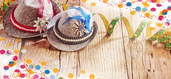 Oktoberfest carnival background with Bavarian hats. Oktoberfest carnival banner background with Bavarian hats, twirled streamers and colorful confetti around stock photo