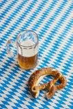 Oktoberfest: Ciambellina salata e birra sulla tovaglia bavarese Fotografia Stock