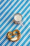 Oktoberfest: Ciambellina salata e birra sulla tovaglia bavarese Fotografia Stock Libera da Diritti